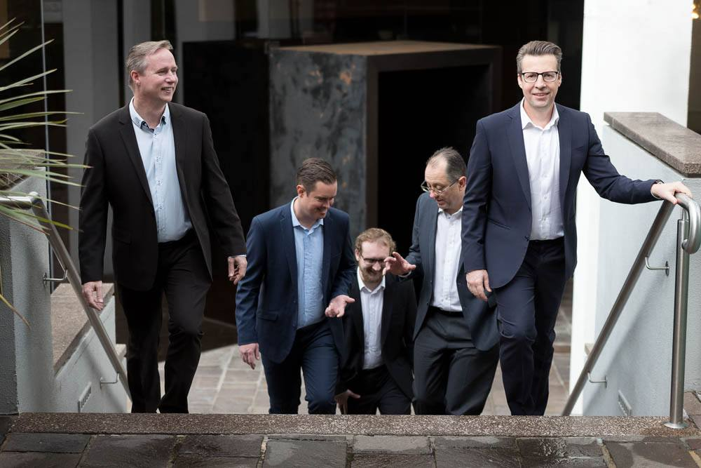 Five men in suits walking up the stairs, smiling.