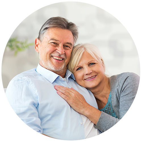 Older man and woman smiling and hugging on a couch.