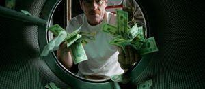 A man holding a bunch of cash he has hidden.